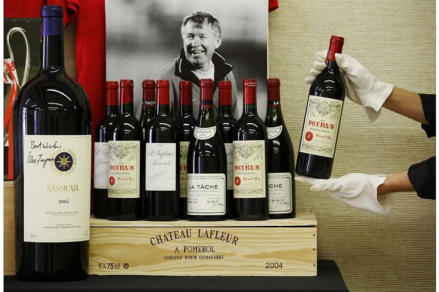 An employee poses with a selection of fine and rare wines owned by retired Manchester United boss Alex Ferguson, at Christie's auction house in London on April 14, 2014. -- PHOTO: REUTERS