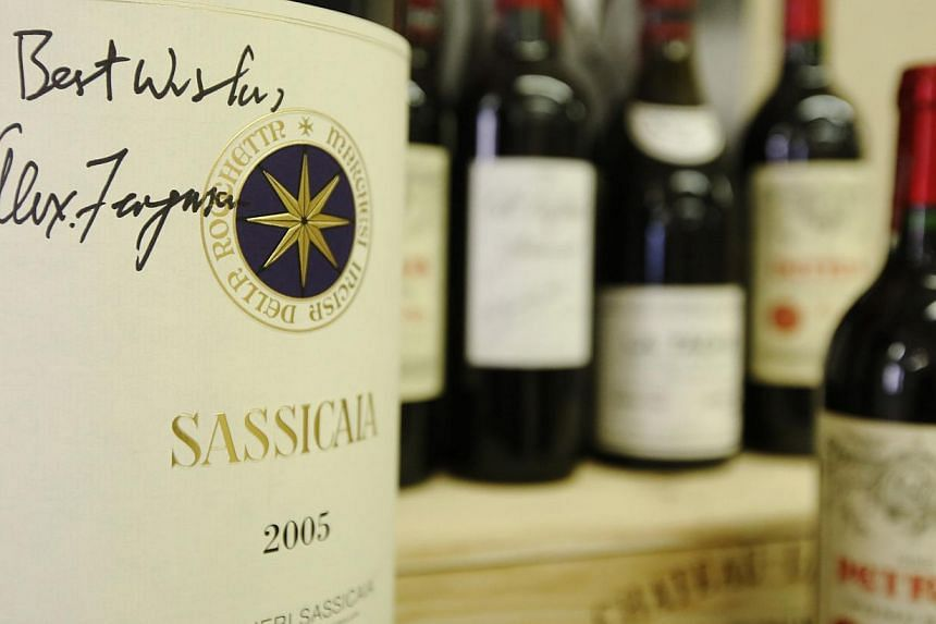 """A six litre imperiale """"Sassicaia 2005"""" wine, signed by retired Manchester United boss Alex Ferguson, is seen with other wines owned by Ferguson, at Christie's auction house in London on April 14, 2014. -- PHOTO: REUTERS"""