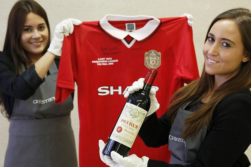"""Employees pose with a bottle of """"Petrus 1988"""" wine and a Manchester United Retro Champions League shirt from 1999 signed by retired boss Alex Ferguson, at Christie's auction house in London on April 14, 2014. -- PHOTO: REUTERS"""