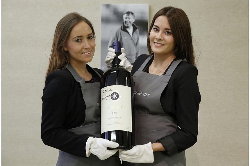 "Employees pose with a six litre imperiale ""Sassicaia 2005"" wine, signed by retired Manchester United boss Alex Ferguson, at Christie's auction house in London on April 14, 2014. -- PHOTO: REUTERS"