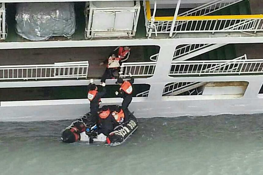 This South Korea Coast Guard handout photo taken at sea some 20km off the island of Byungpoong in Jindo on April 16, 2014, shows South Korea Coast Guard members rescuing some of the passengers and crew aboard a South Korean ferry sinking on its way t