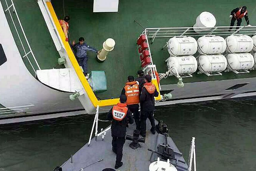 A passenger is rescued by South Korean maritime policemen from a sinking ship Sewol in the sea off Jindo on April 16, 2014, in this picture provided by Korea Coast Guard and released by Yonhap. -- PHOTO: REUTERS