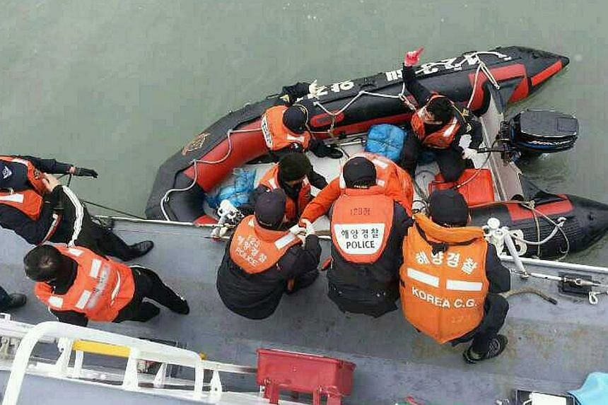 This South Korea Coast Guard handout photo taken at sea some 20km off the island of Byungpoong in Jindo on April 16, 2014 shows South Korea Coast Guard members rescuing some of the passengers and crew aboard a South Korean ferry sinking on its way to