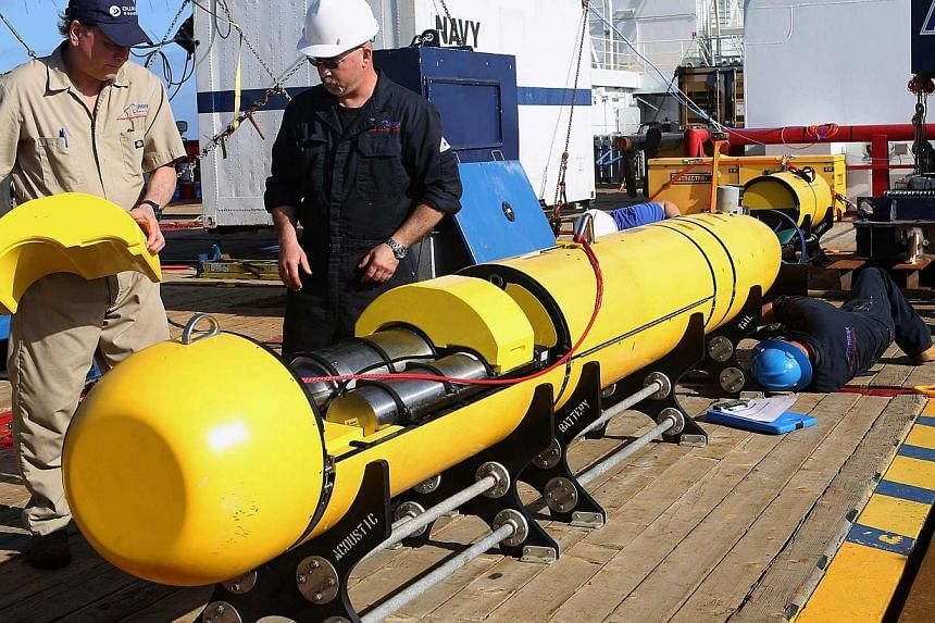 Phoenix International workers inspect the United States Navy's Bluefin 21 autonomous underwater vehicle before deployment in the southern Indian Ocean to look for the missing Malaysia Airlines flight MH370 in this handout picture released by the Au
