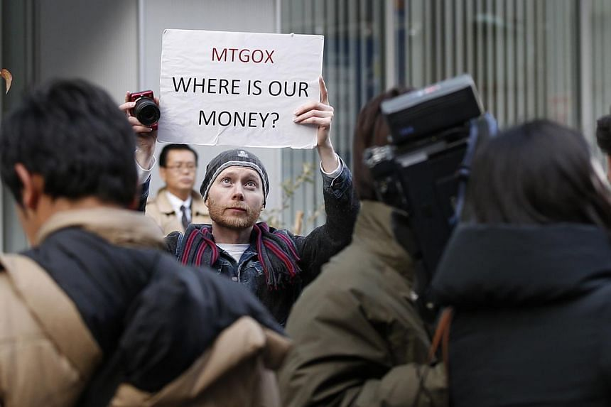 Kolin Burges, a self-styled cryptocurrency trader and former software engineer from London, holds up a placard to protest against Mt. Gox, in front of the building where the digital marketplace operator was formerly housed in Tokyo, on Feb 26, 2014.