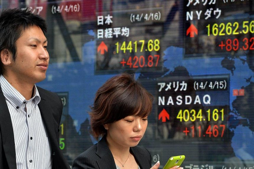 Pedestrians walk in front of a share prices board illustrating the numbers for various world stock markets in Tokyo on April 16, 2014. Tokyo's Nikkei stock index jumped 3.01 per cent Wednesday as bargain-buying and a weaker yen lifted the Japanese ma