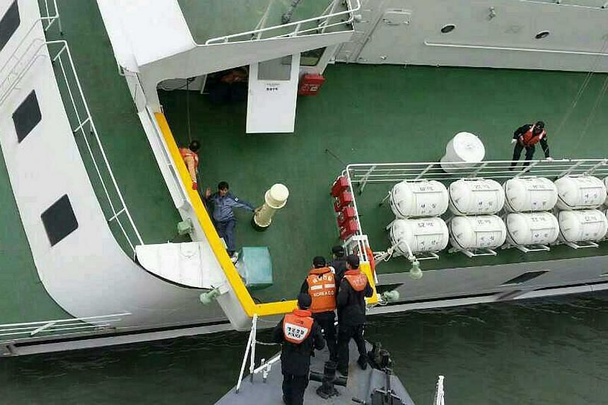 South Korea Coast Guard members rescuing some of the passengers and crew aboard a South Korean ferry sinking on its way to Jeju island from Incheon, on April 16, 2014. The South Korean coast guard said on Wednesday more than 300 people were unaccount