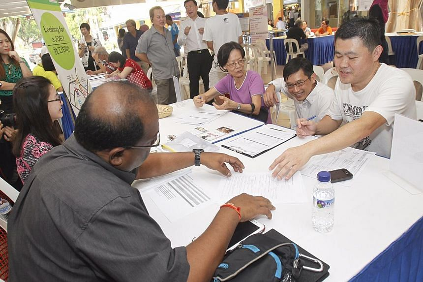Mayor of North East CDC Teo Ser Luck chats with job applicants Madam Mary Tan, 70, and Mr Ser Ah Chin, 44, at a recruitment Drive by North East CDC to promote employment opportunities that are available within the heartlands for the local residents a