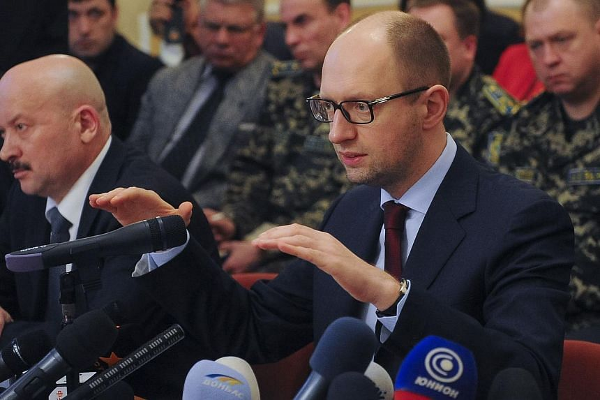 "Ukraine's Prime Minister Arseny Yatseniuk (right) delivers a speech as he attends a meeting in Donetsk, on April 11, 2014.  Ukraine's prime minister on Wednesday, April 16, 2014, accused Russia of ""exporting terrorism"" to Ukraine by using covert"