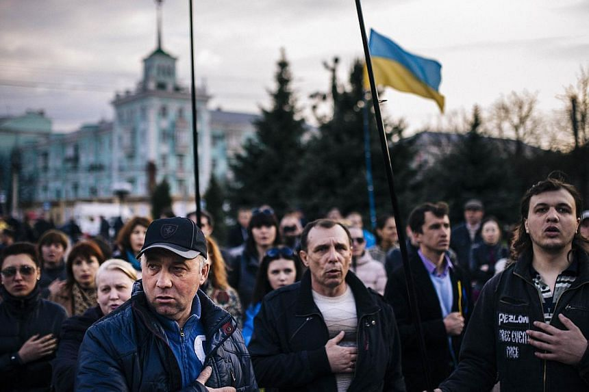 People sing the Ukrainian national anthem during a pro-Ukraine rally in the eastern Ukrainian city of Lugansk, on April 15, 2014. Ukraine's defence minister said on Wednesday, April 16, 2014, that pro-Russian militants had taken two of its soldiers ""