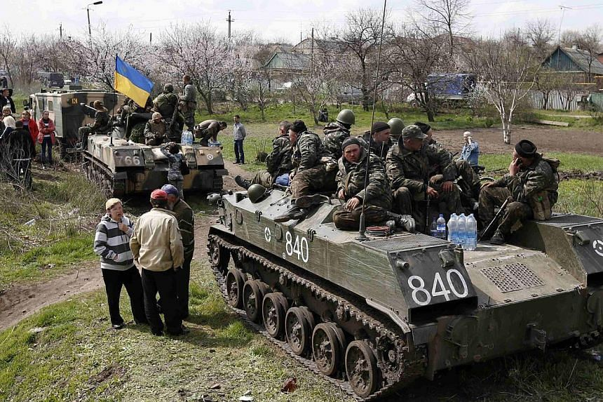 Ukrainian soldiers sit on top of armoured personnel carriers while surrounded by pro-Russia protesters in Kramatorsk, in eastern Ukraine, on April 16, 2014. Ukraine's security service said on Wednesday that its intercepted communications showed that