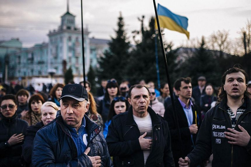 People sing the Ukrainian national anthem during a pro-Ukraine rally in the eastern Ukrainian city of Lugansk on April 15, 2014. The United States has threatened Russia with new sanctions ahead of high-stakes talks on the Ukraine crisis, as it backed