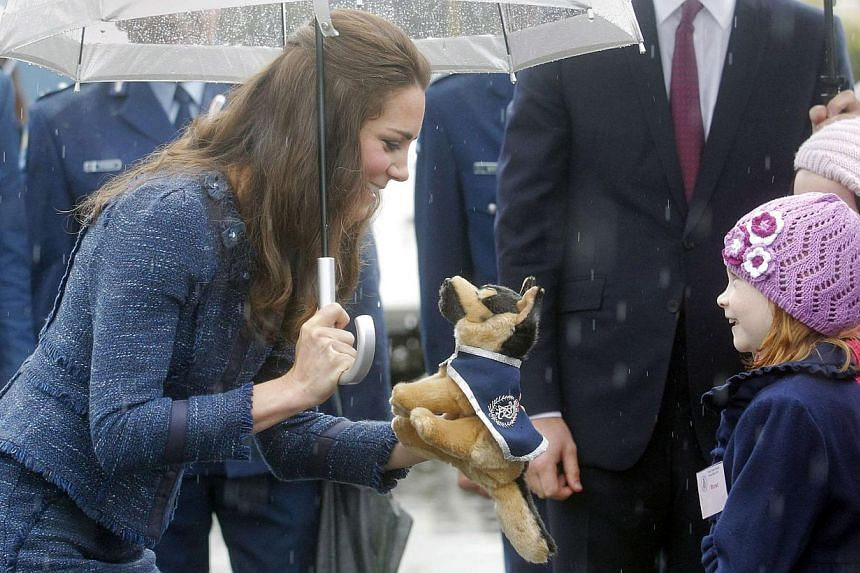 Catherine, the Duchess of Cambridge, receives a toy dog from a young girl as she tours with her husband, Britain's Prince William, the Royal New Zealand Police College in Wellington on April 16, 2014. -- FILE PHOTO: REUTERS