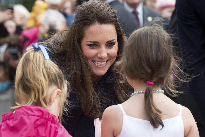 Catherine, the Duchess of Cambridge, speaks to two girls presenting her with flowers during a walkabout with Britain's Prince William (not pictured) in Civic Square, Wellington, on April 16, 2014. -- PHOTO: REUTERS