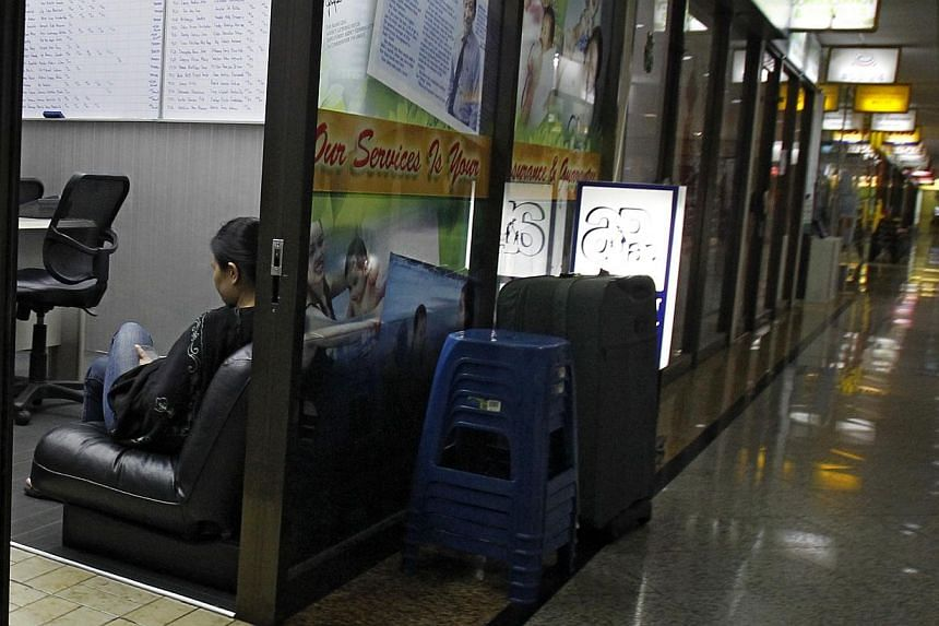 A maid sits inside a maid employment agency in Coronation Plaza on March 14, 2014. -- ST FILE PHOTO: WANG HUI FEN