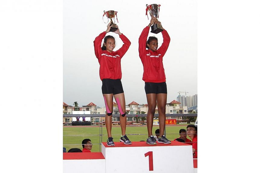 Nur Izlyn (left) and Kugapriya, captains of the Singapore Sports School's B Division Girls team, lifting the challenge and championship trophies. -- ST PHOTO: ONG WEE JIN