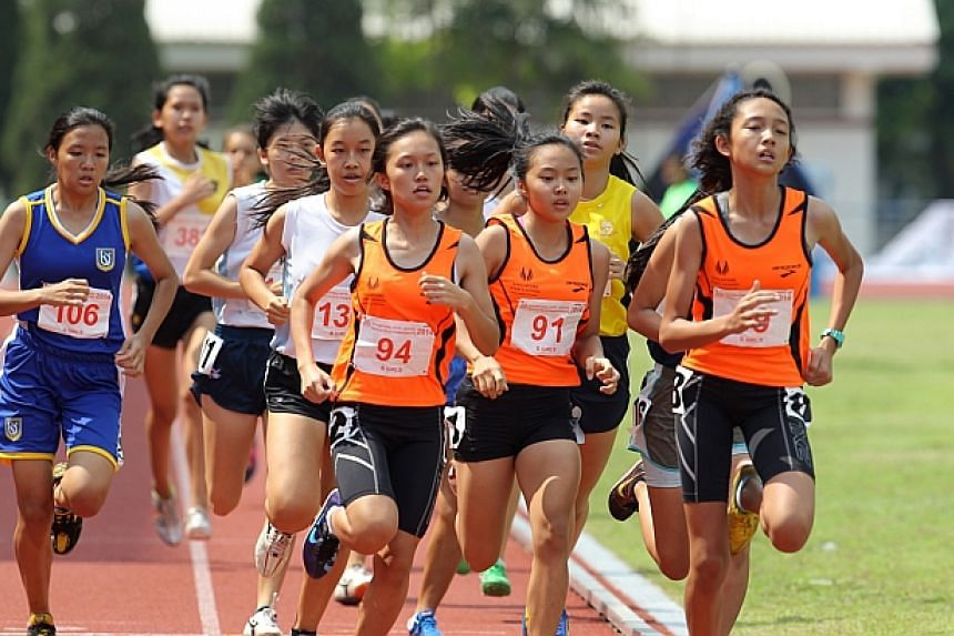 The Singapore Sports School's Grace Ng (94), Celeste Goh (91) and Addeen Idzni Imran (89) leading the pack during the 800m B Girls final at the Schools National Track and Field Championships. -- ST PHOTO: ONG WEE JIN