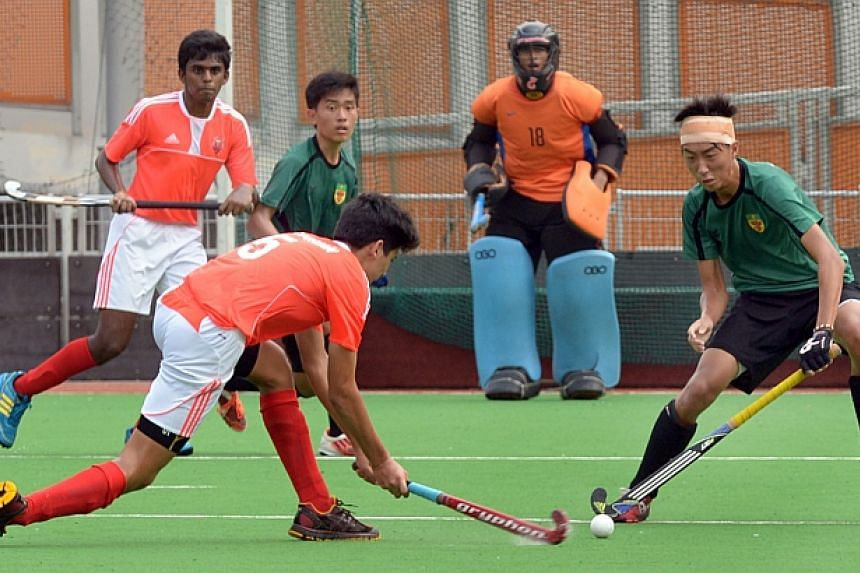 Raffles Institution (in green) and Victoria School players in action in the National Schools 11-a-side hockey B division boys' final.-- ST PHOTO: LIM SIN THAI