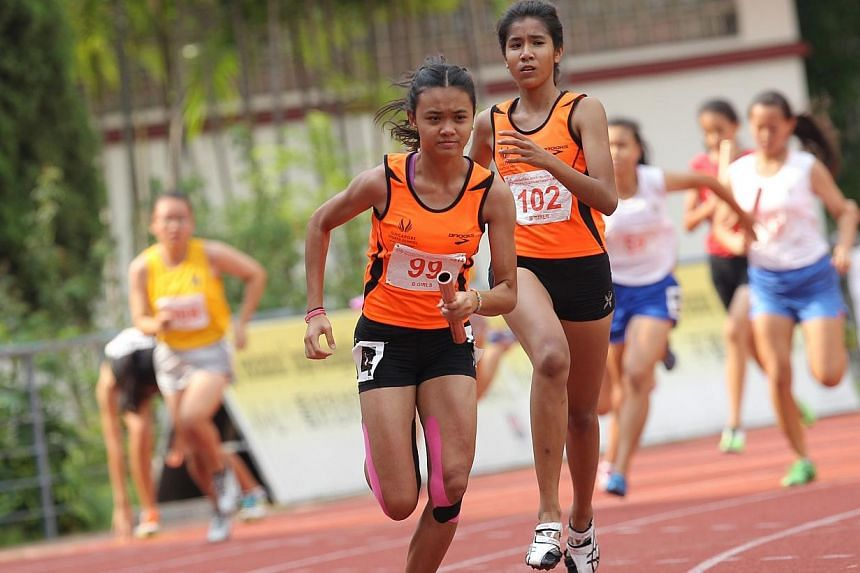 The Singapore Sports School's Sarah Nadia passing the baton to anchor runner Nur Izlyn (left) in the B Division 4x100m relay event. -- ST PHOTO: ONG WEE JIN