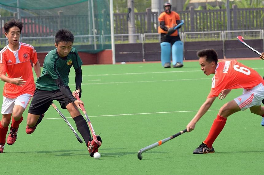 Raffles Institution (in green) and Victoria School players in action in the National Schools 11-a-side hockey B division boys' final. -- ST PHOTO: LIM SIN THAI