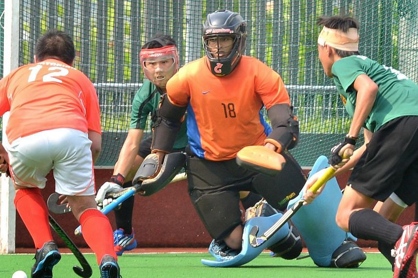 A Victoria School player (left) scores against Raffles Institution in the National Schools 11-a-side hockey B division boys' final. -- ST PHOTO: LIM SIN THAI
