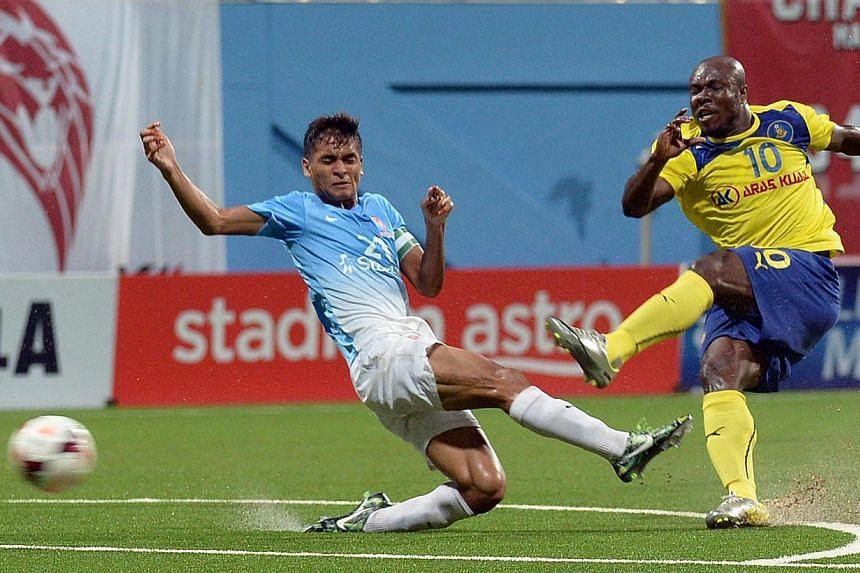 Pahang's danger man Dickson Nwakaeme attempts to score as LionsXII captain Safuwan Baharudin tries to stop him.-- ST PHOTO: DESMOND WEE