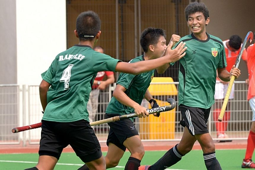 A Raffles Institution player (right) celebrates after scoring the first goal. -- ST PHOTO: LIM SIN THAI