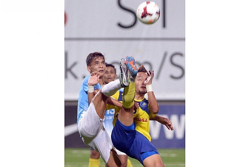 Safuwan Baharudin (left) and Azidan Sarudin go for the ball. -- ST PHOTO: LIM SIN THAI