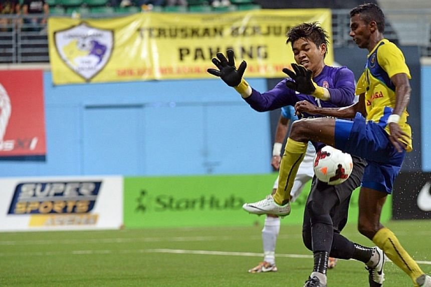 LionsXII's goalkeeper Izwan Mahbud attempts to get the ball from Pahang's Gopinathan Ramachandra. -- ST PHOTO: DESMOND WEE