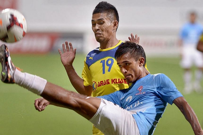 Shakir Hamzah (front) gets the ball away from Fauzi Rozlan. -- ST PHOTO: LIM SIN THAI