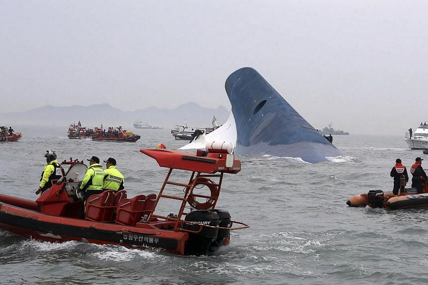 A part of South Korean passenger ship Sewol is seen as South Korean maritime policemen search for passengers in the sea off Jindo on Wednesday, April 16, 2014. -- PHOTO: REUTERS