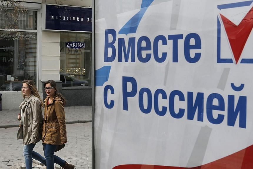 """People walk past a board which reads """"Together with Russia"""" in the Crimean city of Simferopol on April 7, 2014.The United States is coordinating with its European allies on """"additional steps"""" to slap more sanctions on Russia over the crisis in"""