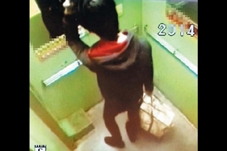 CCTV footage of Chung in an elevator looking in the mirror while carrying a bag said to contain his son's body. -- PHOTO: DAEGU DONGBU POLICE STATION