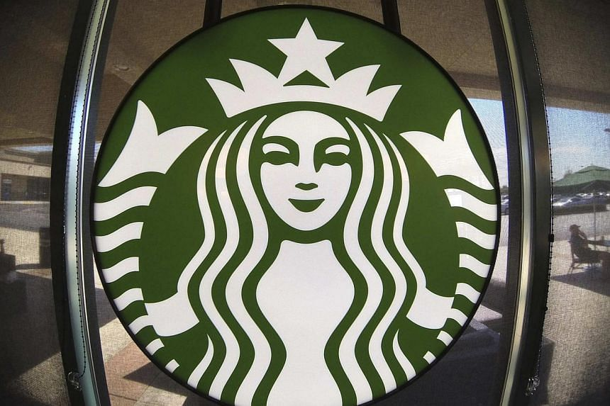 The Starbucks logo hangs on a window inside a newly designed Starbucks coffee shop in Fountain Valley, California in this file photo from August 22, 2013. Starbucks said it decided to move its European headquarters to Britain from the Netherlands fol