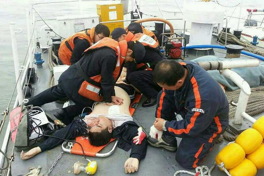 An injured passenger who was on a sinking ship, is rescued by South Korean maritime policemen, in the sea off Jindo April 16, 2014 in this picture provided by West Regional Headquarters Korea Coast Guard and released by News1. One person has been fou