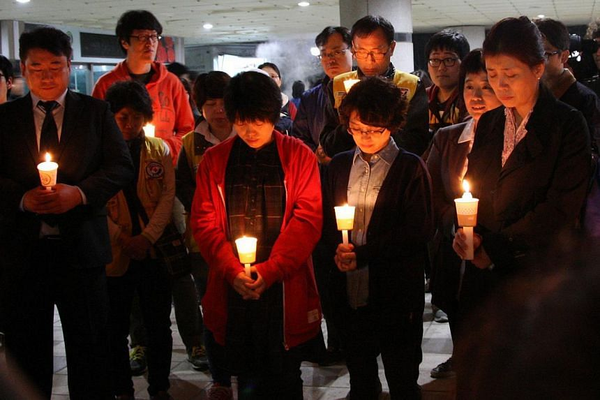 Family members of missing students who were on the South Korean ferry Sewol which sank in the sea off Jindo attend a candlelight vigil at Danwon High School in Ansan on April 16, 2014. -- PHOTO: REUTERS