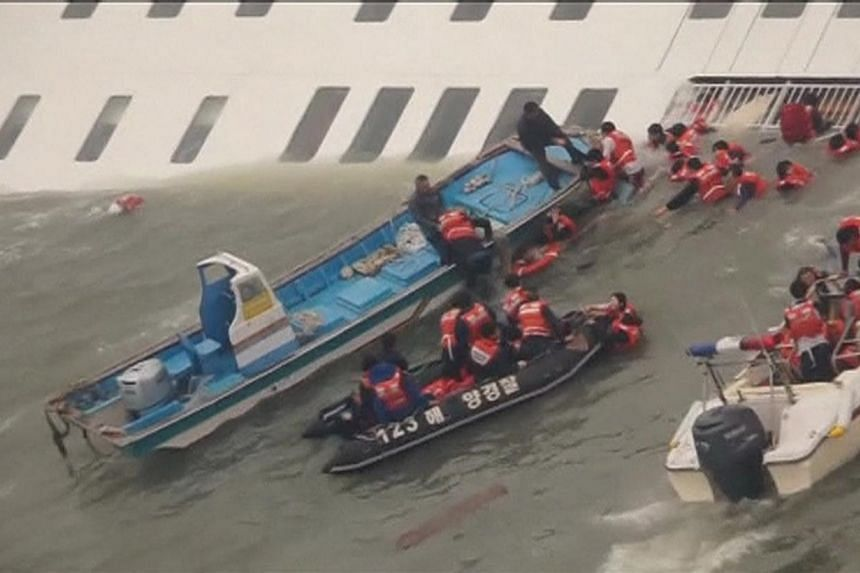 Members of the South Korean coast guard rescue passengers from the water next to a partially sunken ferry, off South Korea's southwest coast in this still image from a video released by the South Korean coast guard on April 16, 2014. -- PHOTO: REUTER