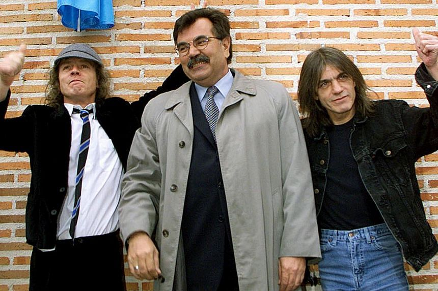Angus (left) and Malcolm (right) Young, founder members of Australian heavy metal band AC/DC, flank Jose Luis Perez, mayor of the Madrid district of Leganes, following the inauguration of a new street with the group's name on March 22, 2000. AC/