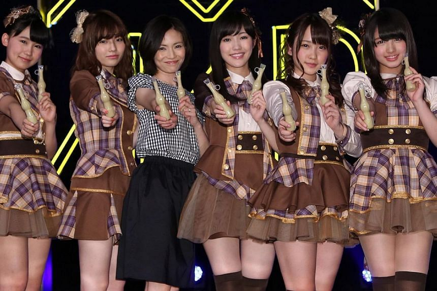 """Mariko Tsukamoto (3rd left), a 37-year-old housewife, smiles as she poses with members of AKB48 after winning membership of """"Otona (adult) AKB48"""" in Yokohama, suburban Tokyo on April 17, 2014, after being picked from a pool of over 5,000 applicants i"""