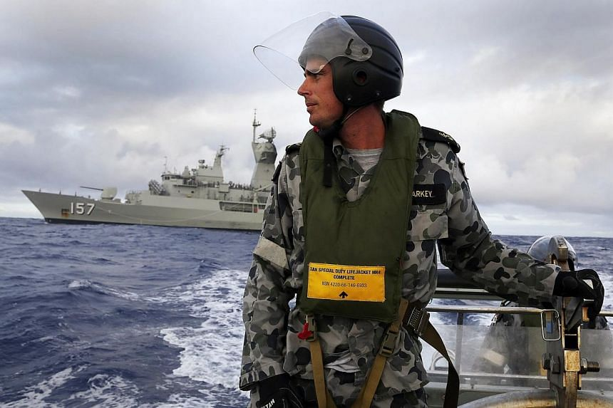 Standing in a rigid hull inflatable boat launched from the Australian Navy ship HMAS Perth, a seaman searches for possible debris in the southern Indian Ocean in the continuing search for the missing Malaysian Airlines flight MH370. An oil slick