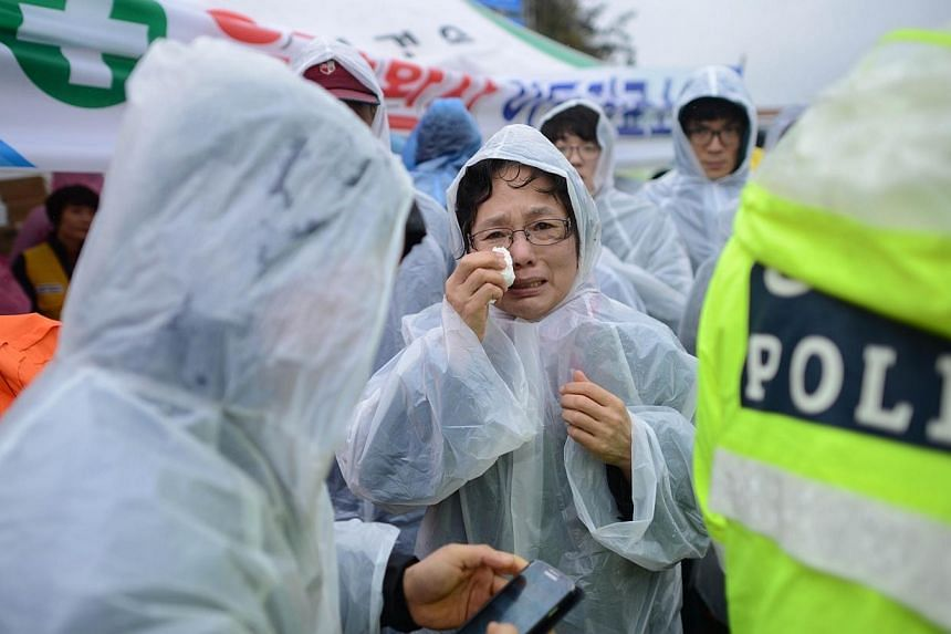 A relative (centre) reacts as she waits in a makeshift tent along a dockside in Jindo on April 17, 2014, as the frantic search for nearly 300 people, most of them schoolchildren, missing after a South Korean ferry capsized extended into a second day,