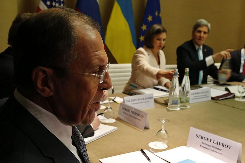 Russian Foreign Minister Sergei Lavrov (left) looks on as US Secretary of State John Kerry (second from right) starts a quadrilateral meeting between representatives of the United States, Ukraine, Russia and the European Union about the ongoing situa