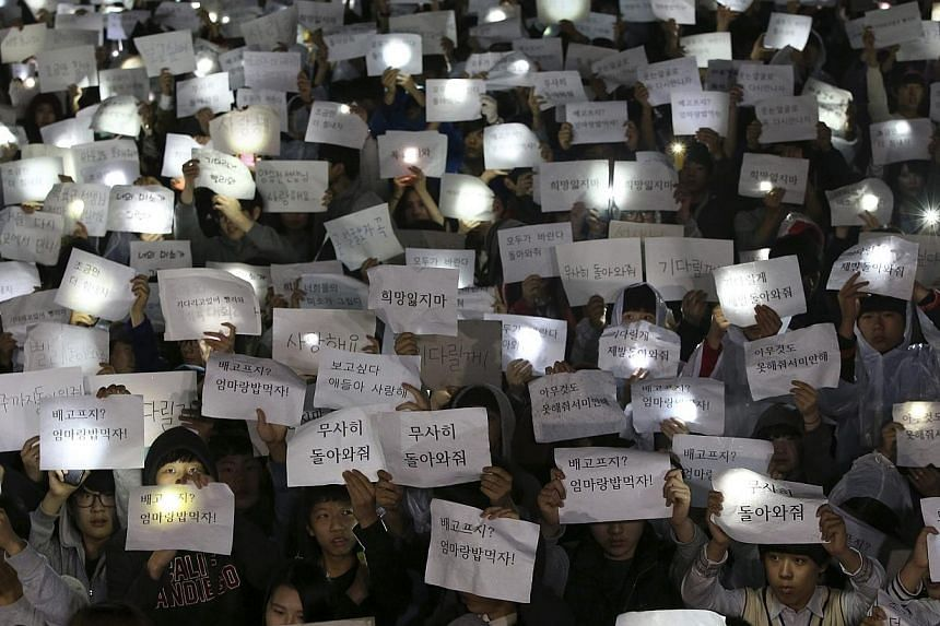Students hold signs with messages of hope for the return of their missing friends who were on the Sewol ferry, which sank in the sea off Jindo, at Danwon High School in Ansan on April 17, 2014. -- PHOTO: REUTERS