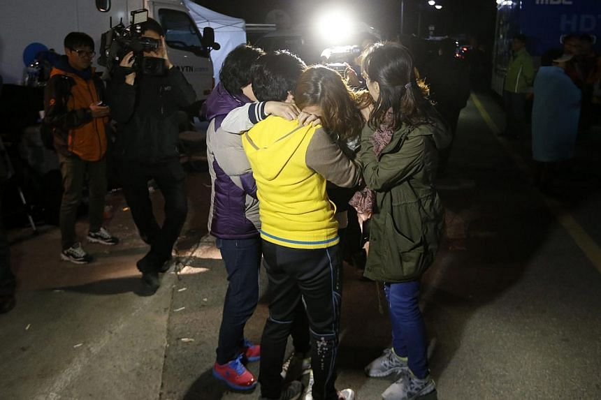 """Family members of missing passengers who were on the South Korean ferry """"Sewol"""" which sank in the sea off Jindo cry as they wait for a rescue team's arrival at a port. -- PHOTO: REUTERS"""