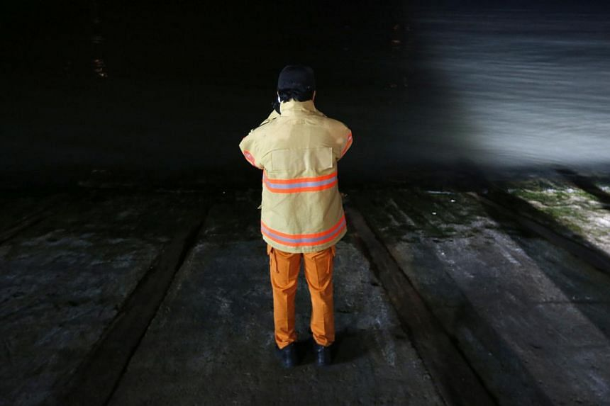 A rescue worker wait for a rescue team's arrival at a port where family members of missing passengers gathered in Jindo April 16, 2014. More than 280 people, many of them students from the same high school, were missing after a ferry capsized off Sou