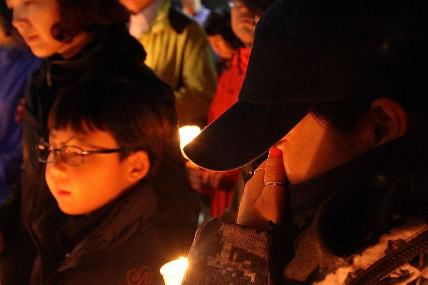 """Family members of missing students who were on a South Korean ferry """"Sewol"""" which sank in the sea off Jindo attend a candlelight vigil at Danwon High School in Ansan. -- PHOTO: REUTERS/YONHAP"""