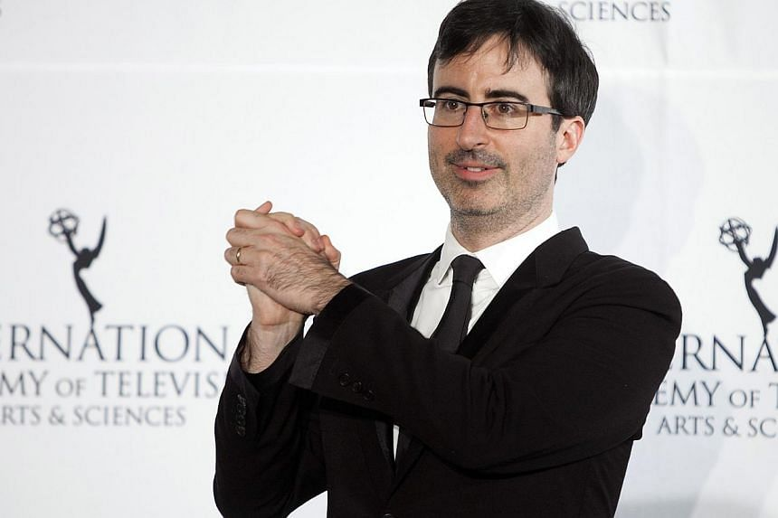 Comedian John Oliver poses for photographers backstage during the 41st International Emmy Awards in New York in this file photo taken November 25, 2013. The 36-year-old has managed to parlay a successful stint filling in for Jon Stewart on The D