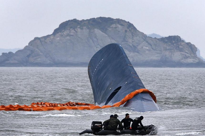 A vessel involved in salvage operations passes near the upturned South Korean ferry Sewol in the sea off Jindo on April 17, 2014. National shock at a ferry disaster that may have claimed the lives of hundreds of South Korean schoolchildren was mixed