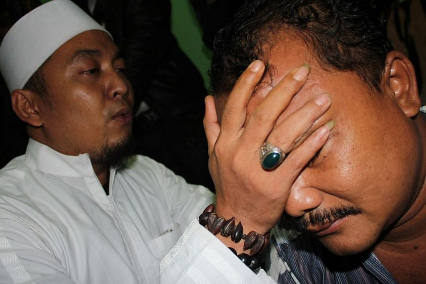In this photograph taken on April 10, 2014, Sofyan, (right) an Indonesian candidate in the local legislative election in Cirebon district in Java island is undergoing treatment for stress by an unidentified Islamic cleric in Cirebon. Many of the