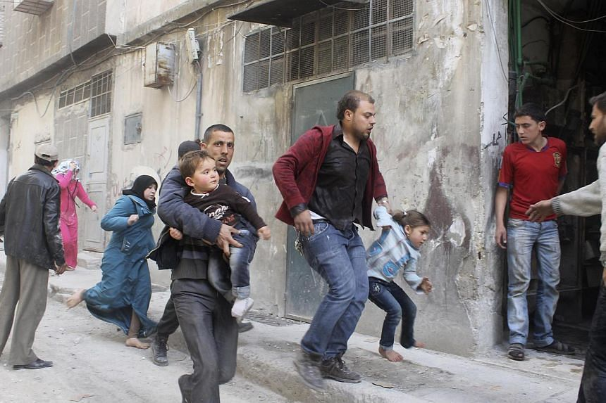 Residents run to take cover after what activists said was a barrel bomb dropped by forces loyal to Syria's President Bashar al-Assad in Aleppo's al-Myassar neighbourhood on April 16, 2014. Syria is the world's most dangerous country for journali